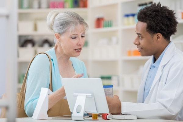 African American pharmacy technician male talking to a customer in a drugstore