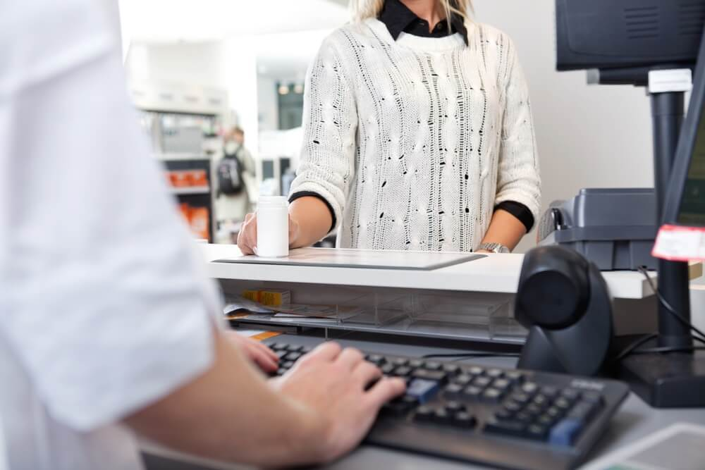 A pharmacy technician in a retail pharmacy at checkout with a customer.