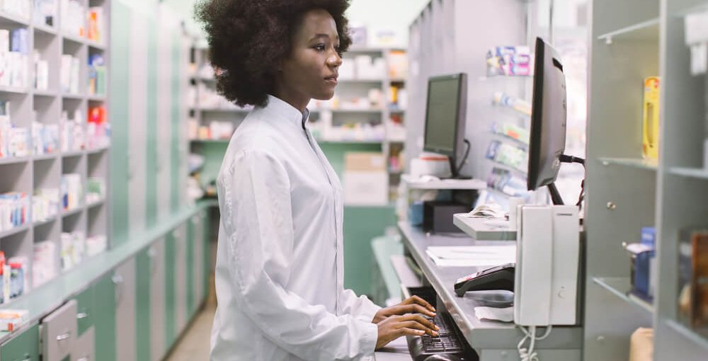 A young female pharmacy technician working behind a counter in a drug store
