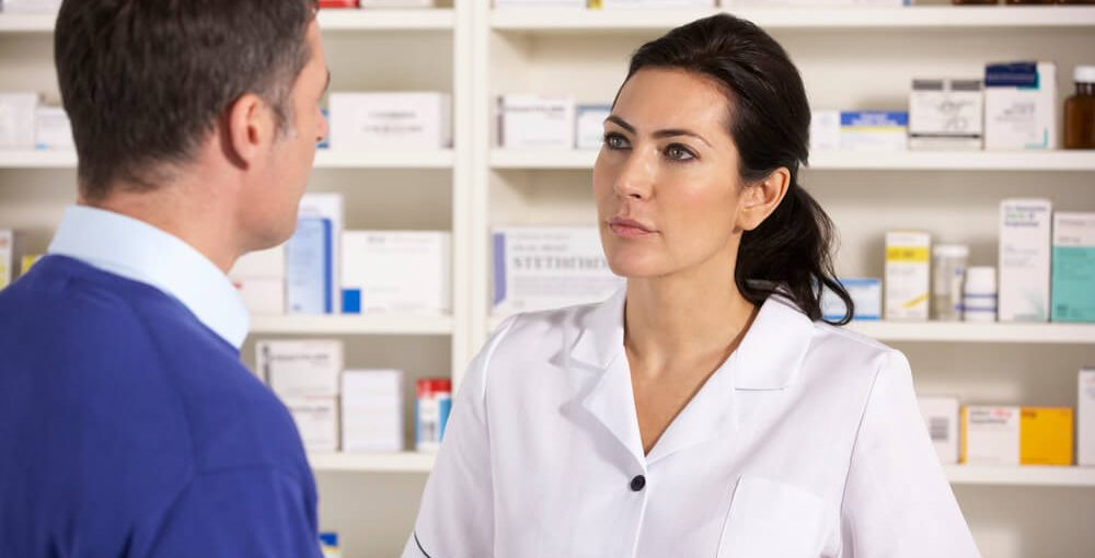 Female pharmacist technician talking to a customer in a pharmacy