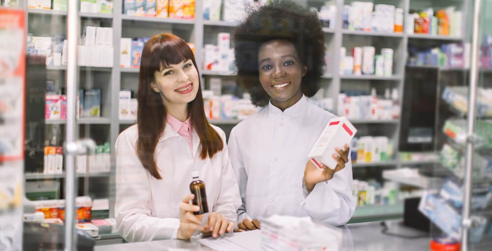 Two female pharmacy technicians working behind a counter in a pharmacy
