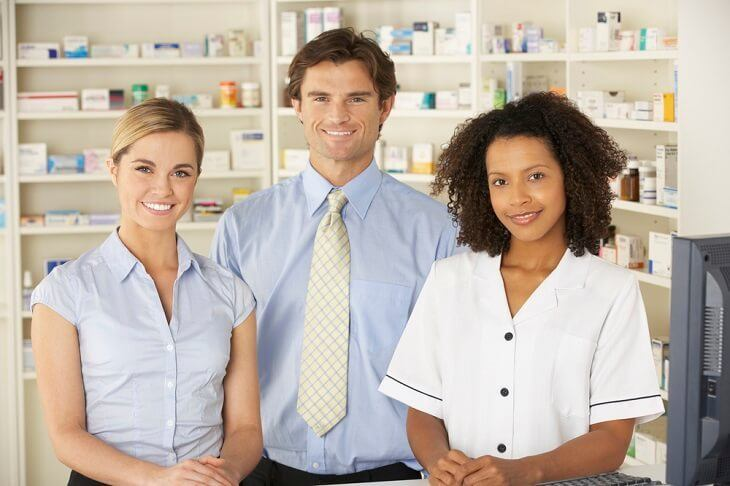 Female and male pharmacist and pharmacist technician behind a counter in a retail pharmacy technician.