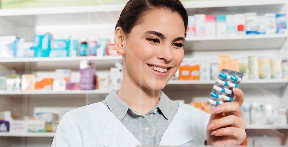 A young female pharmacy technician working in a retail pharmacy setting