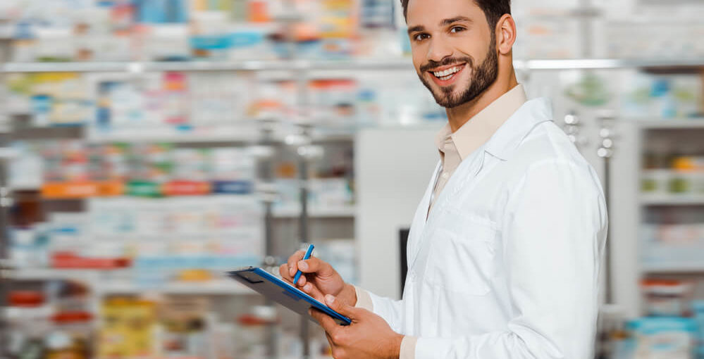 A young male pharmacy technician working in a retail pharmacy setting