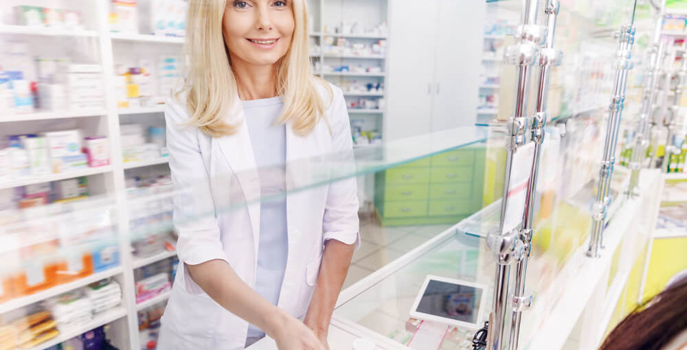 A mature pharmacy technician female serving a customer at the till in a drugstore.