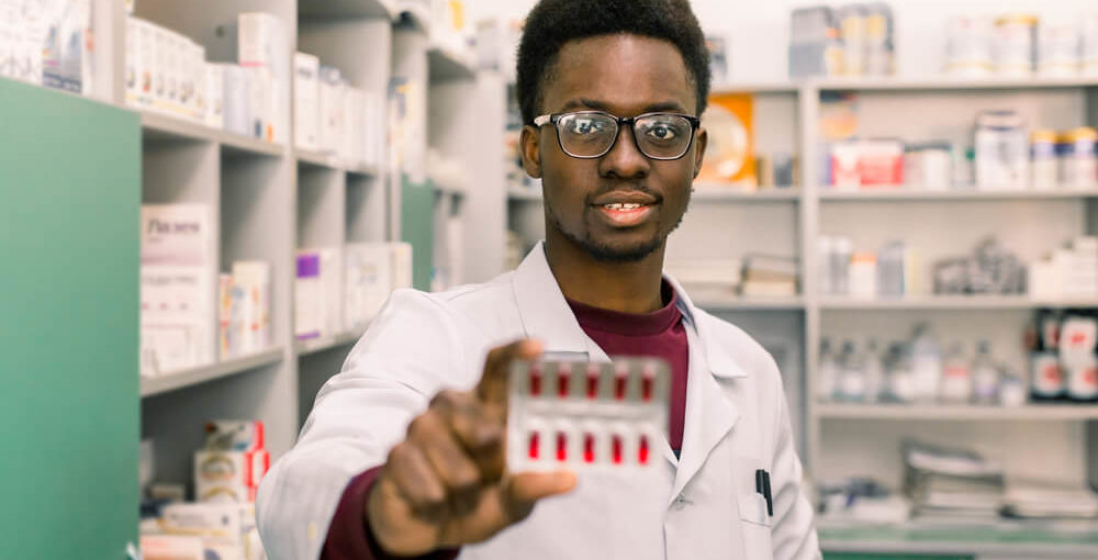 A young male pharmacy technician wearing a white lab coat holding a packet of drugs in a retail pharmacy