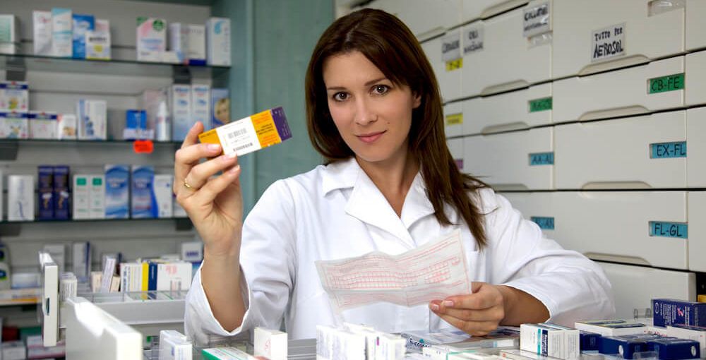 A female pharmacy technician holding up antibiotics from a prescription in a retail pharmacy