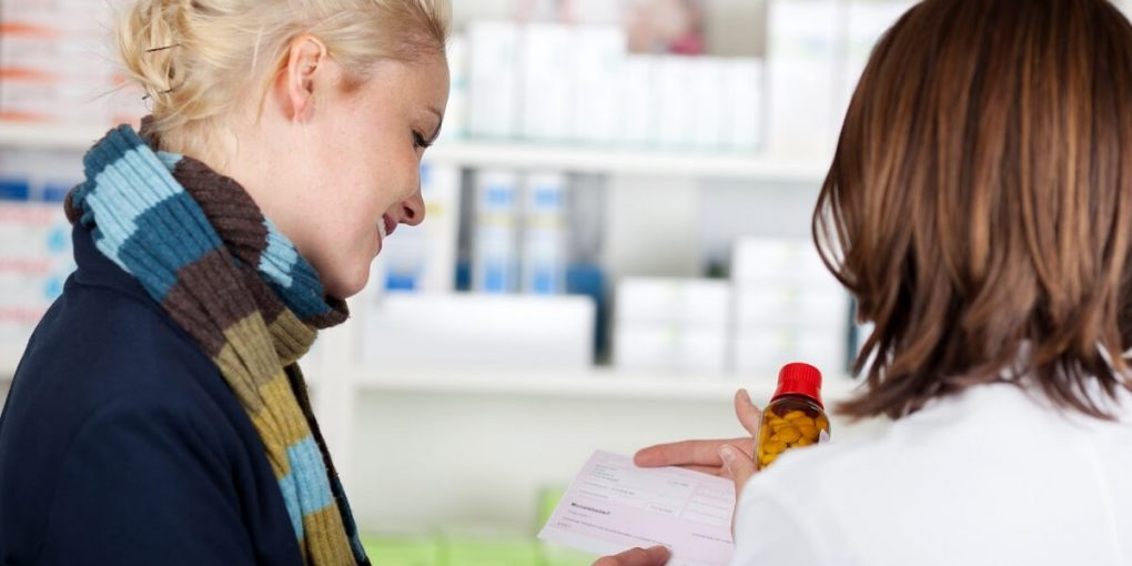 A customer with a prescription in a retail pharmacy and a pharmacy tech.