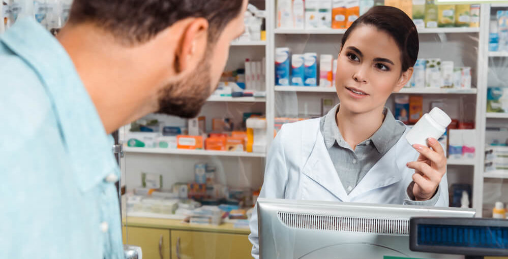 A newly trained pharmacy technician behind the till in a drug store selling a bottle of pills to a male customer