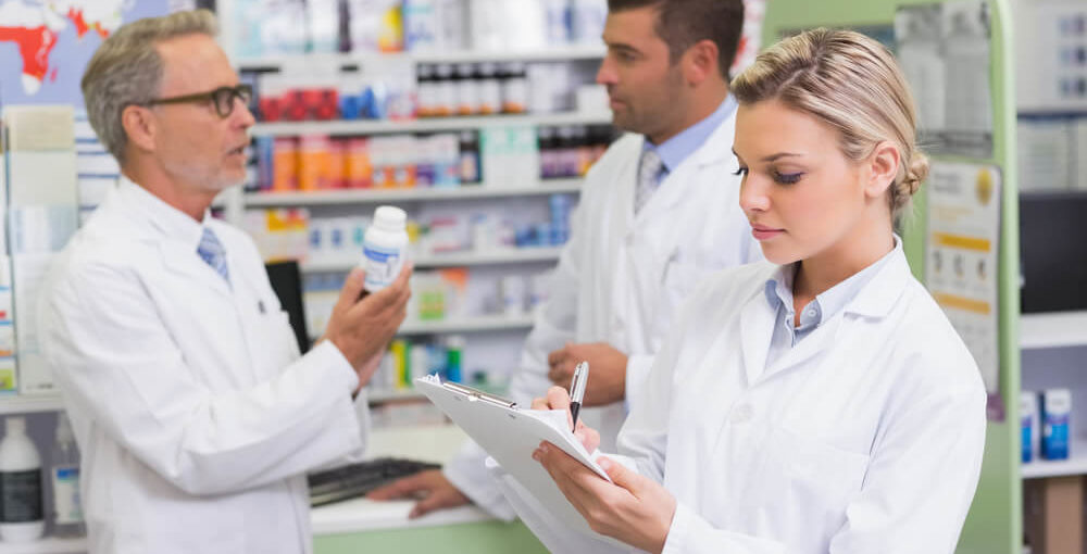 A male and female pharmacy technician working alongside a pharmacist in a retail pharmacy